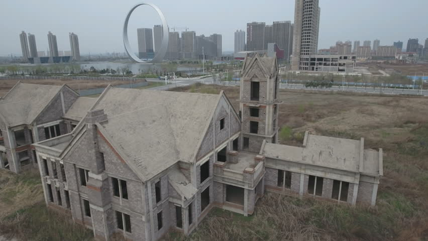 Flying away from an empty building (partly under construction) revealing a large 'ghost city' in Liaoning province, China