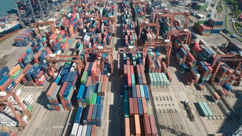 HONG KONG, CHINA - JULY 2016: Tilted aerial footage (shot by a drone) flying over the colorful container terminal in Hong Kong, tracking a (seemingly tiny) cargo truck.