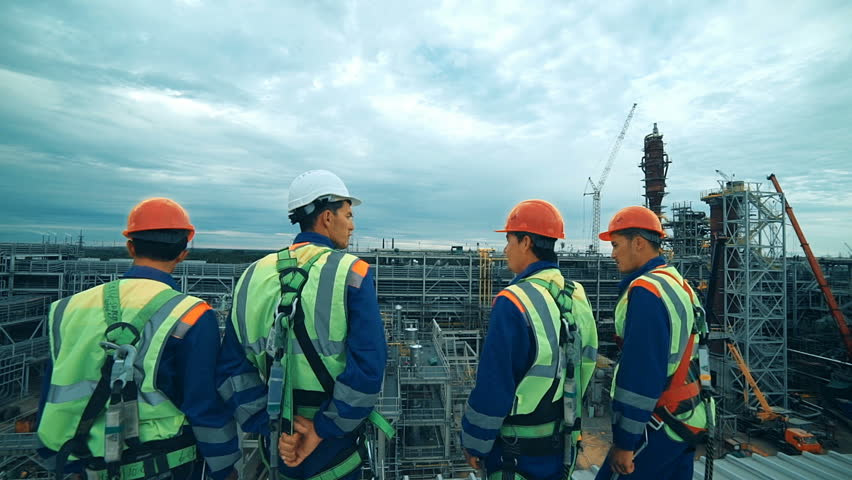 Workers at refinery as team discussing, industrial scene in background.   Shutterstock HD Video #19847104