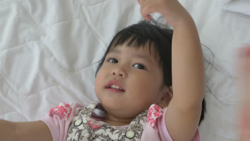 4K : Little Asian child laying and playing on the bed   Shutterstock HD Video #19853671