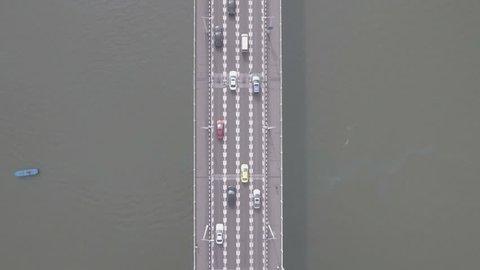 Overhead aerial view of seemingly miniature cars driving over a bridge in Chongqing across the Yangtze river in China. D-log profile DJI Phantom.