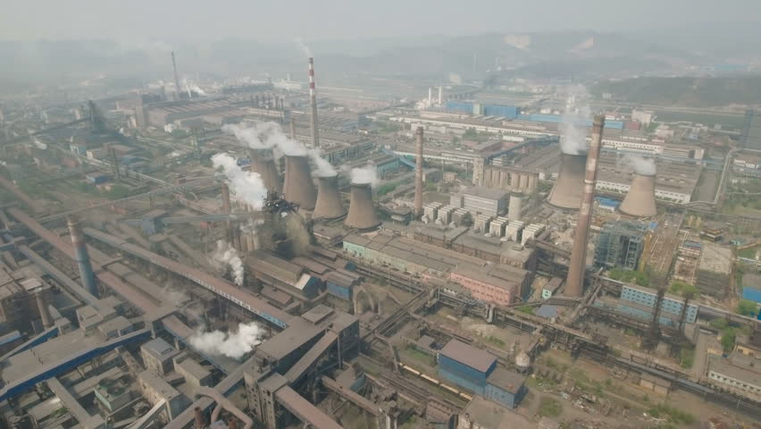 Overhead aerial footage of reactors on the site of a large steel mill (manufacturer, producer) in the heavy industrial city of Benxi in Northern China.