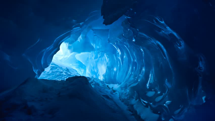 Blue ice cave covered with snow and flooded with light. Slow motion 4K footage
