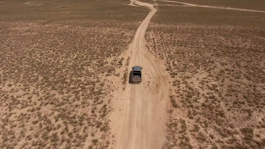 American Delivery Service overcomes difficult roads that would deliver a valuable cargo to its client on remote ranch in the distance from modern infrastructure. Road trip to Australia. Aerial photo