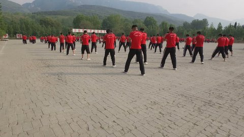 SHAOLIN, CHINA - MAY 2016: Groups of kung fu martial arts students practice at the training grounds of a large institute in Wushu, the 'birthplace' of kung fu in central China