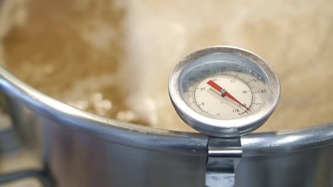 Stainless steel kitchen thermometer measures the temperature of boiling wort beer homebrew ( warm tone color )