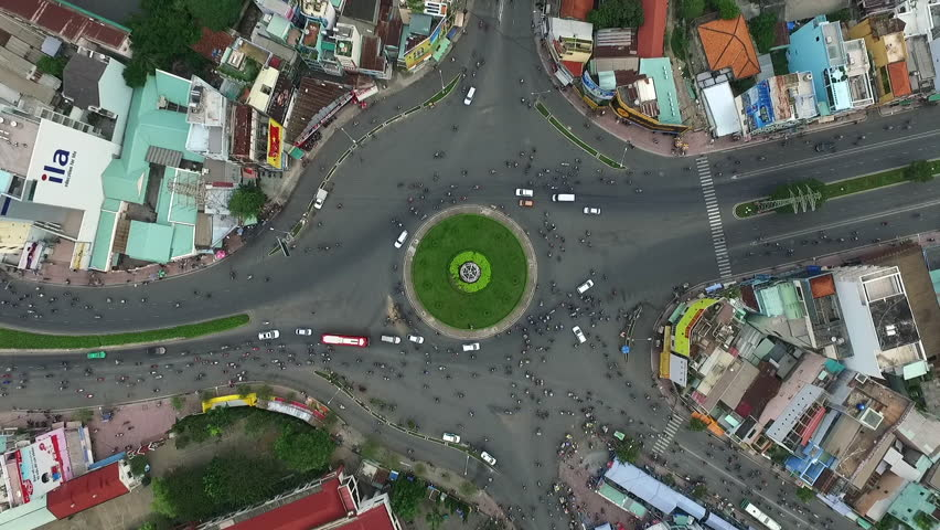 Aerial city view, flying over a city, a suggestive perpendicular aerial video above a traffic roundabout with a lot of traffic