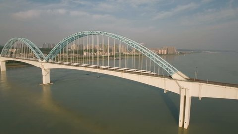 Aerial drone flight towards a beautiful bridge across the Yangtze river. A high speed bullet train rides over the bridge. Infrastructure in China.