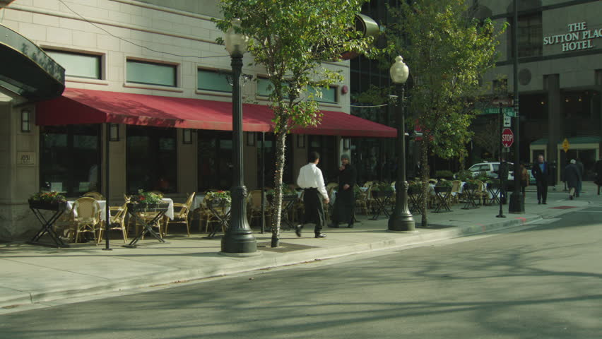 Day , left nice restaurant fir street floor modern stone building, red awning over patio tables front, large windows right, small green curved awning | Shutterstock HD Video #19952971