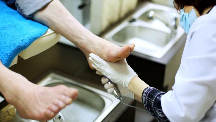 Cosmetician grinds man heel on doing pedicure in beauty salon