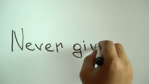 """Hand writing title """"Never give up"""" using a black marker on a white board"""
