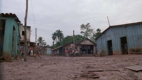 day Low angle very poor Latin American village foreign jungle village dirt road shack style buildings, palms impoverished people Brazil, South America