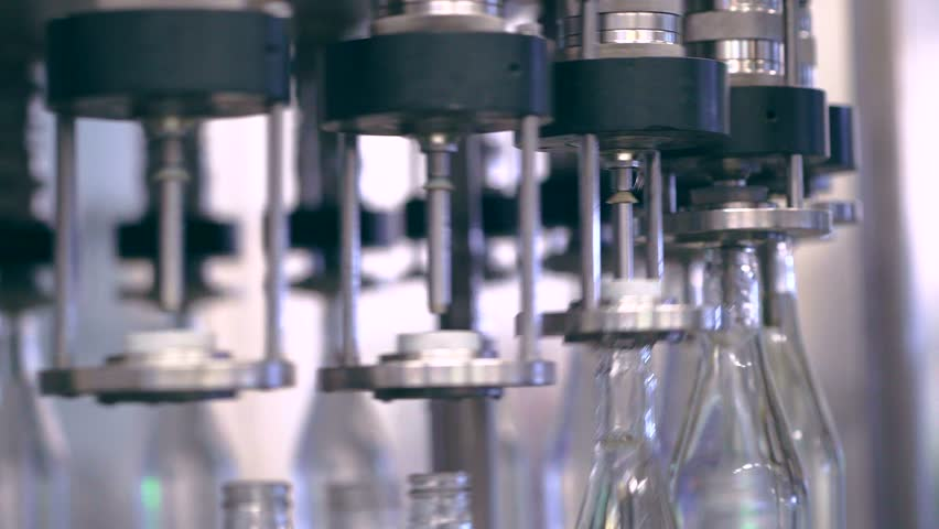 Spill of alcohol in glass bottles at the plant. Conveyor belt with glass bottles. Shop the spillage of alcoholic beverages. Conveyor close-up. The production process of alcoholic beverages. 4K res.