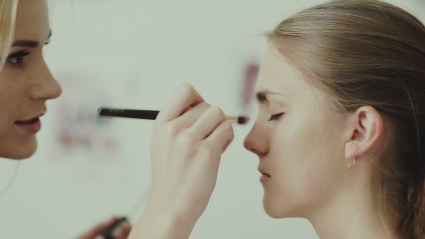 Make-up artist and model. Makeup. Girl makeup with long white hair. Makeup artist applies eye shadow to model. Make-up artist makeup girl s eye using a ...
