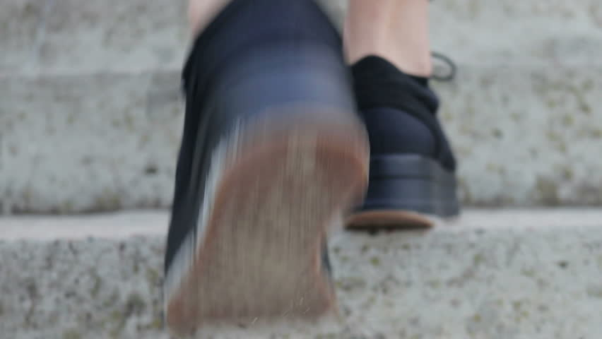 Close-up of female legs in black shoes climbing the stairs, slow motion, low angle shooting