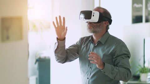 Technology VR - Mature businessman wearing virtual reality technology googles / VR Glasses to work with in modern bright office. This new technology offers new 3D dimensions