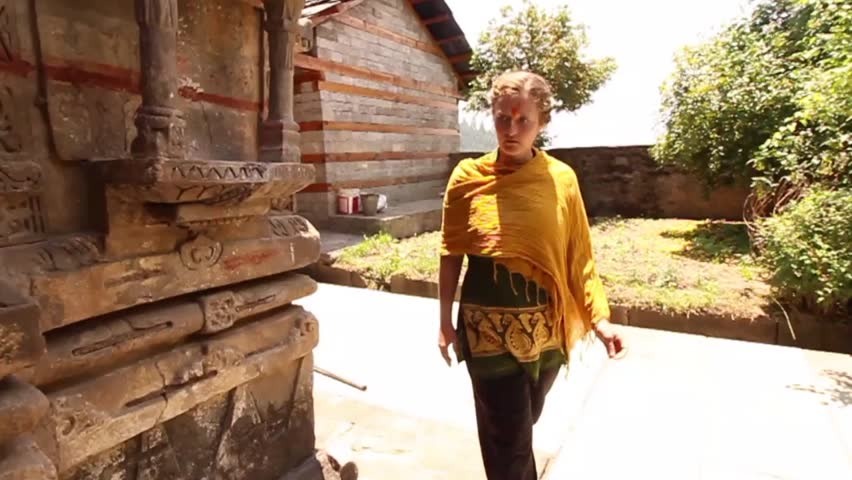 Young woman walks around traditional ancient Krishna Hindu temple in India, slow motion tracking shot, front view