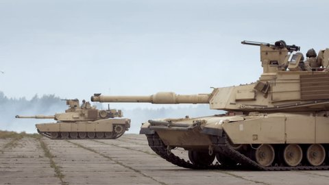 GAIZIUNAI, LITHUANIA - JUNE 18, 2015: M1A2 Abrams tanks in the military base. Two tanks against smoke background during NATO exercise Saber Strike 2015.