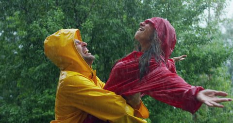 A couple, man and woman in love  dancing, kissing and playing happy smiling under the rain in the nature. freedom and  love. Concept of love, nature, happiness, freedom.