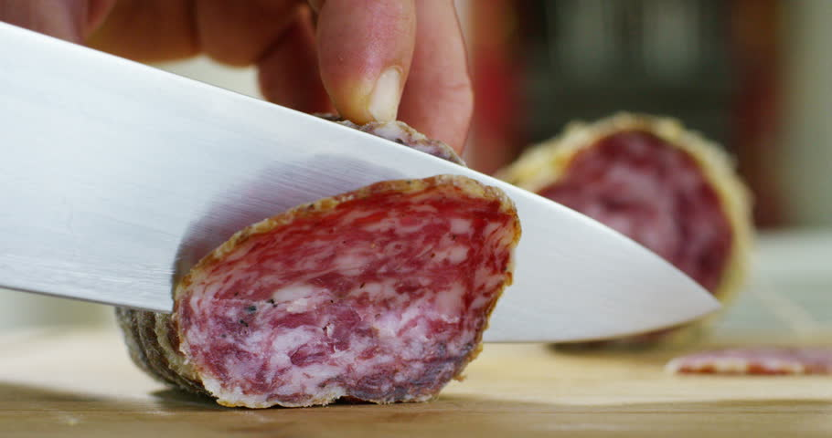 An experienced chef in a professional kitchen cuts the seasoned.Il Italian salami sausage is cut with a professional knife with very thin slices. the concept of nature, Italy, food, diet and bio. | Shutterstock HD Video #20073682