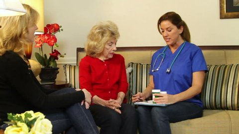 A pretty home health nurse reviews with an elderly patient and her daughter the various prescriptions.