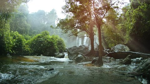 River water slows after a dramatic drop from a natural waterfall. and flows around boulders and trees in Cambodia. with sound.