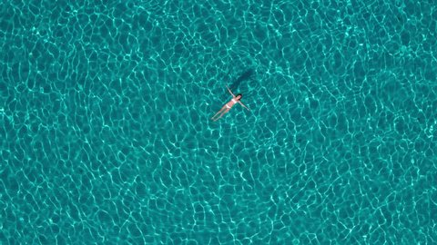 Aerial - Rotating and raising above beautiful young woman floating in crystal clear waters