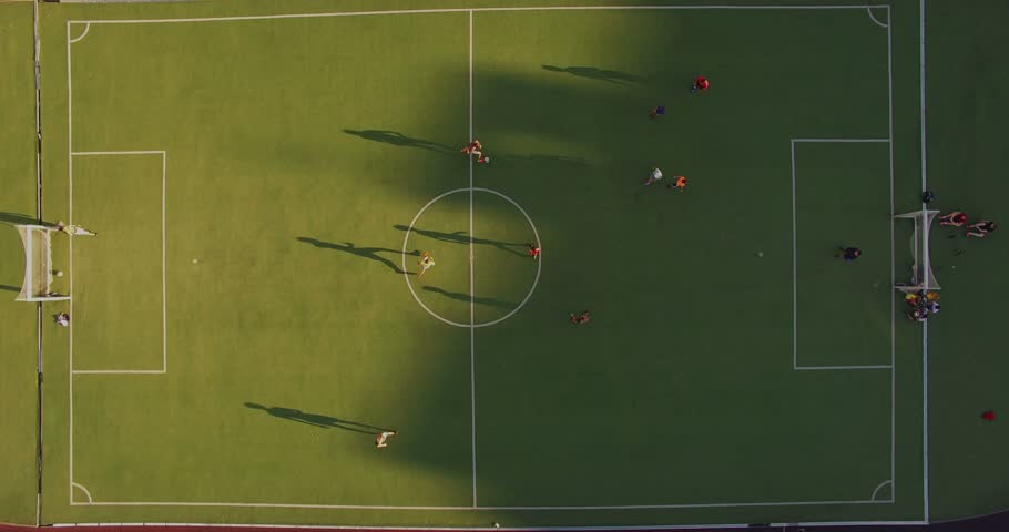Children are playing football. School stadium. Playground. Aerial view. Scores. The ball is at the gate.
