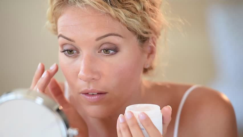 Middle-aged blond woman putting cosmetics on