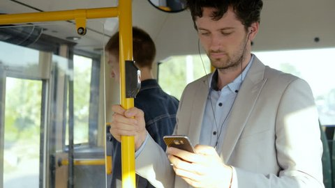 Man starting daily commute with phone. Young man checking an email on his cell phone on the bus.