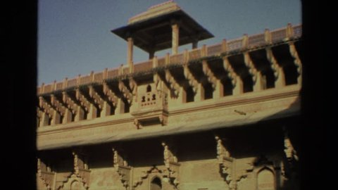 INDIA 1974: an old woman walking in the courtyard of a large amazing building