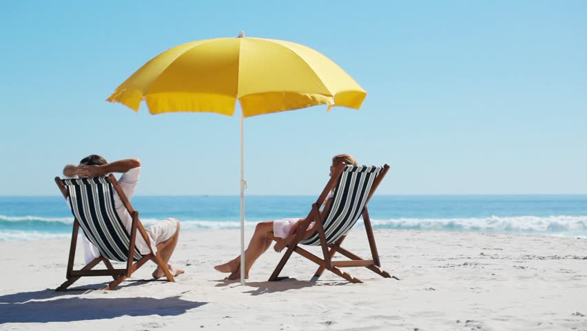 relaxing couple on beach chairs sitting in the sun facing the tropical ocean while on vacation on a tropical island