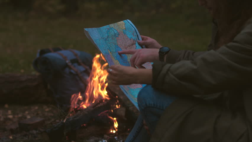 CINEMAGRAPH - Hikers couple studying the map near bonfire. Motion photo seamless loop. 4K UHD RAW edited footage #20158231