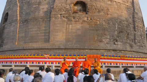 Sarnath,India - February 25,2016: Buddhist monks teach pilgrims at Dhamekh Stupa