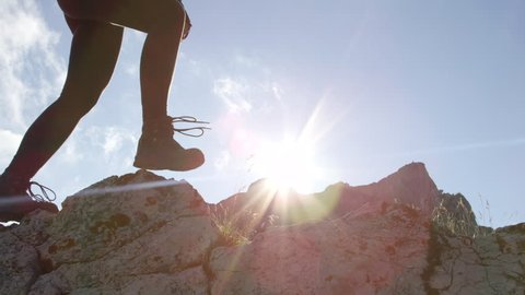 SLOW MOTION, CLOSE UP, LOW ANGLE VIEW: Courageous female hiker climbing mountaintop, walking off trail on dangerous rough rocky mountain ledge. Steep wall opening view of European Alps sunbathing