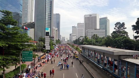 JAKARTA, INDONESIA - SEPTEMBER 25, 2016: People enjoy the car free day, which happens every Sunday morning, on Jalan Sudirman in Indonesia capital city business district.