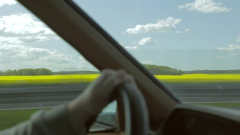 Driving a vintage car on a highway. Fields of yellow flowers outside. View from inside, through window and windshield. Steering wheel with hands on it. Going very fast. Steady, calm shot.