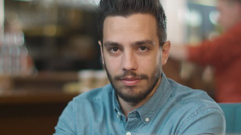 Portrait of Hispanic Ethnicity Young Man at Cozy Coffee Shop. Shot on RED Cinema Camera in 4K (UHD).