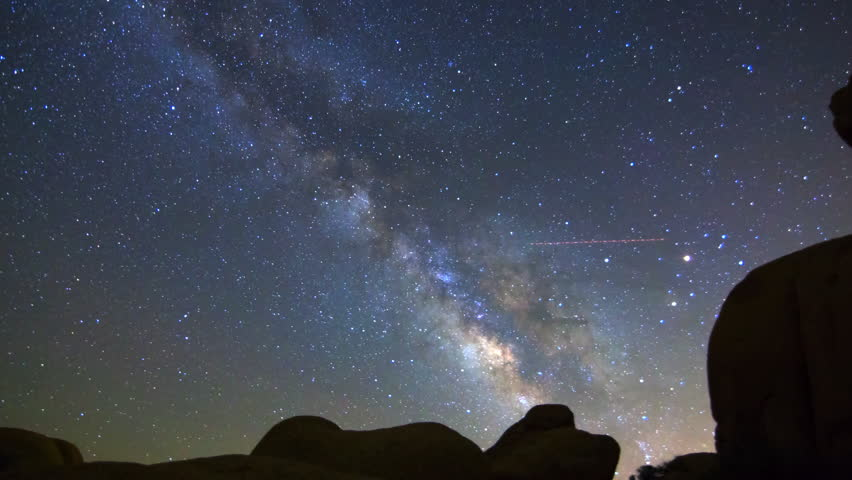 Motion controlled astrophotography time lapse with pan motion of Milky Way galaxy over boulders in Joshua Tree National Park, California