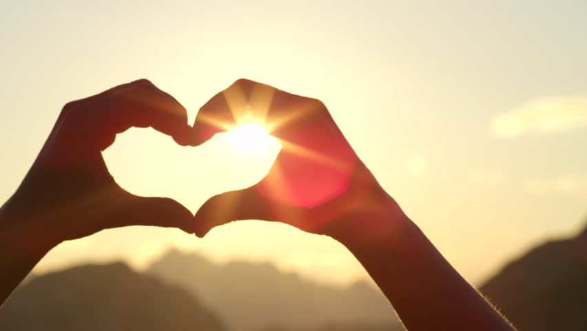 SLOW MOTION, CLOSE UP: Unrecognizable woman catching setting sun with her heart shaped fingers. Young girl making the symbol of love with her hands against stunning golden sky and rising morning sun | Shutterstock Video #20240860