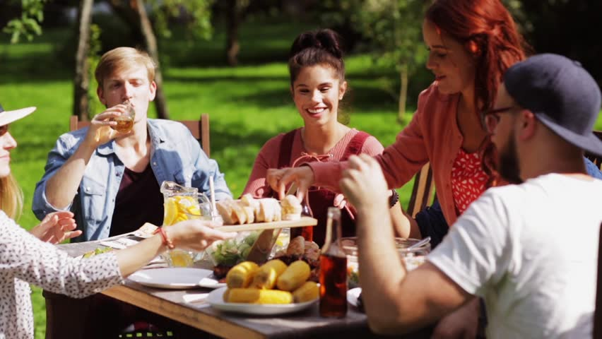 Leisure, holidays, eating, people and food concept - happy friends having dinner at summer garden party | Shutterstock HD Video #20265940