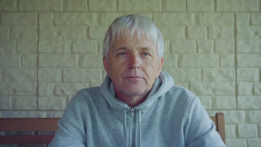 Portrait of old senior man gray hair outside the house sitting on the bench 4K