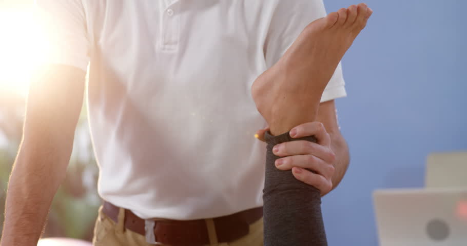 Female patient receiving leg massage from male physiotherapist in clinic | Shutterstock HD Video #20302831