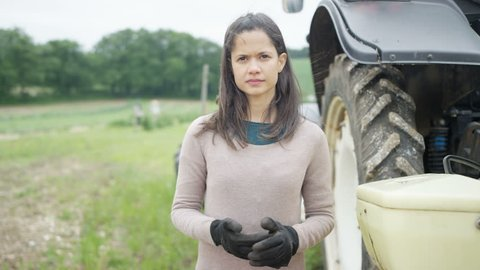 4K Portrait of smiling female farmer standing next to tractor. Shot on RED Epic.