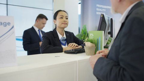 4K Bank worker at service desk assists customer with a cash withdrawal. Shot on RED Epic.