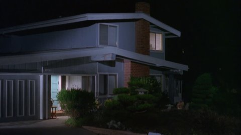 night tight typical 1970s style light blue gray slat wood two story house, brick chimney, porch light right upstairs window light on, then upstairs light turns then up same light turns