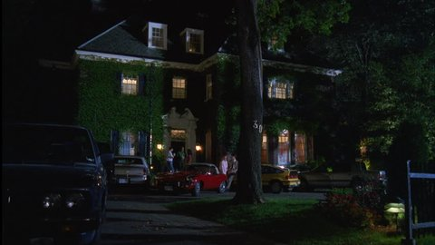 night tilt down bit upscale 3 story brick house mansion, dormers, ivy, many cars, party people hanging out front door couple leaning car, fraternity house