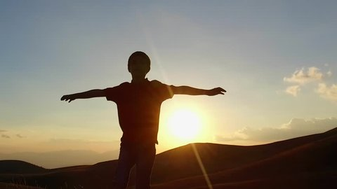 SLOW MOTION: Kid silouette spreading arms and looking to the infinite at the sunset. Conceptual footage.