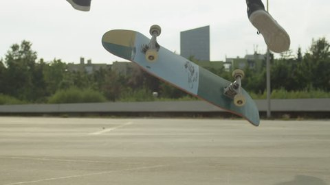 SLOW MOTION CLOSE UP DOF: Unrecognizable skateboarder skateboarding and jumping ollie flip trick on concrete street in sunny summer. Skateboarder jumping kickflip trick with skateboard in the city
