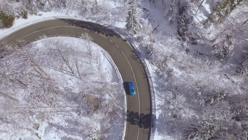AERIAL: Flying above turquoise sport car driving through sharp bend in beautiful snowy forest in sunny winter wonderland. Amazing road trip through picturesque countryside nature in magical wintertime | Shutterstock HD Video #20356261